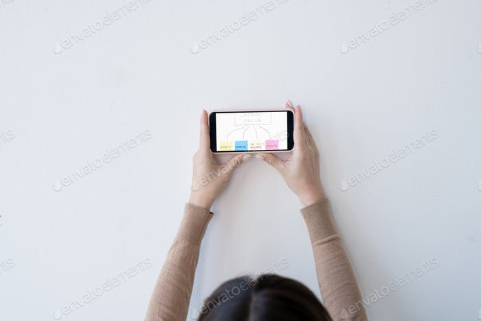 Hands of young businesswoman holding smartphone with decision making flow chart