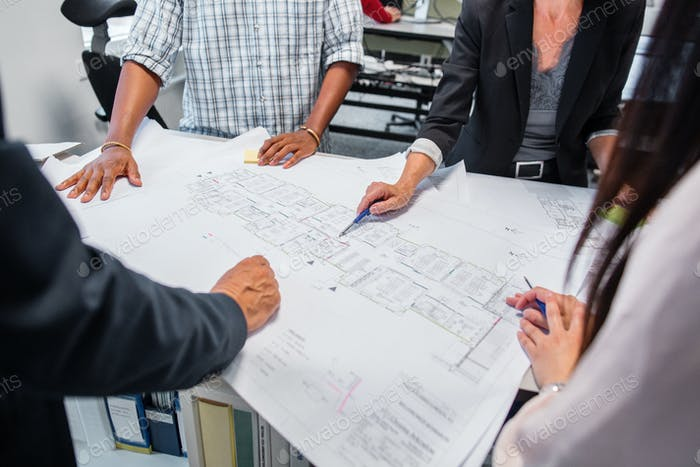 Architects discussing blueprint in office