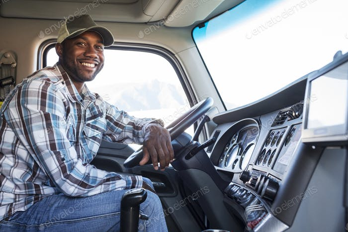 Black man truck driver in the cab of his commercial truck.