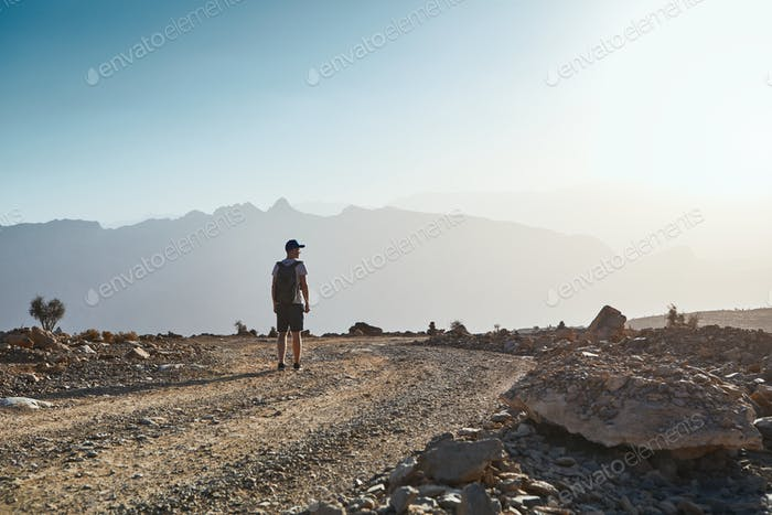 Young tourist on mountain road at sunset
