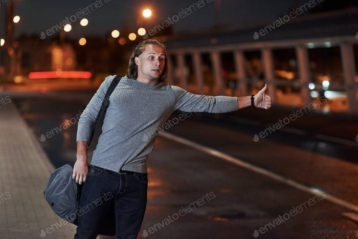 Young man with bag trying to stop the car because he's late
