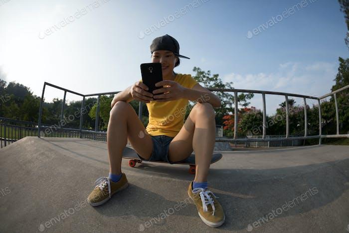 Female skateboarder using mobile phone at skatepark