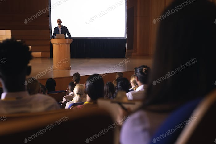Front view of mixed race businessman giving speech in front of audience in the auditorium