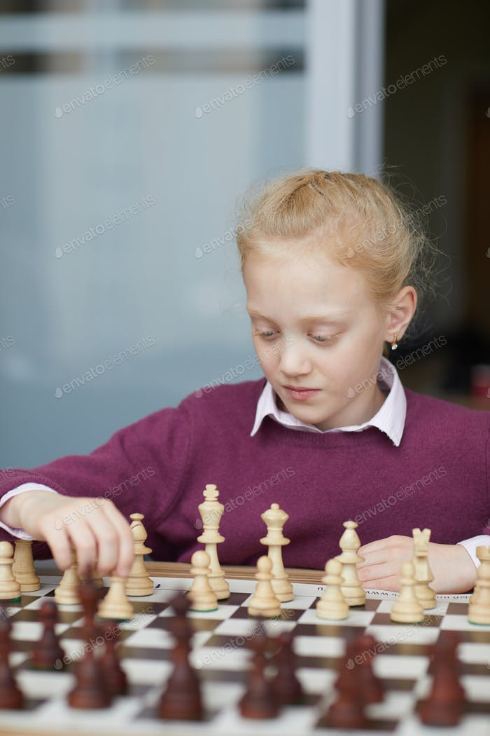 Girl studying chess figures