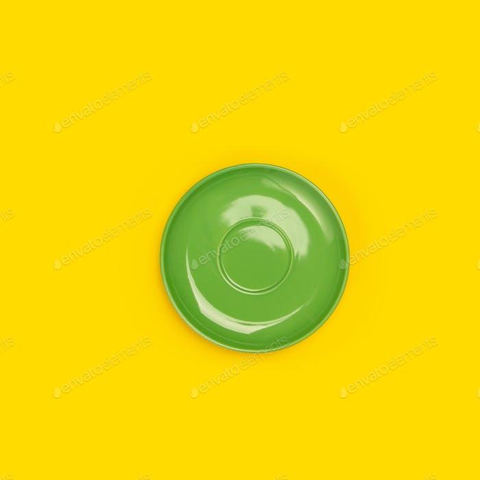 Draufsicht der grünen Keramikplatte (Untertasse) auf gelbem Hintergrund