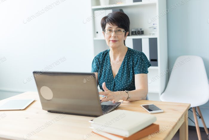 Business people and technology concept - Middle-aged woman working at laptop