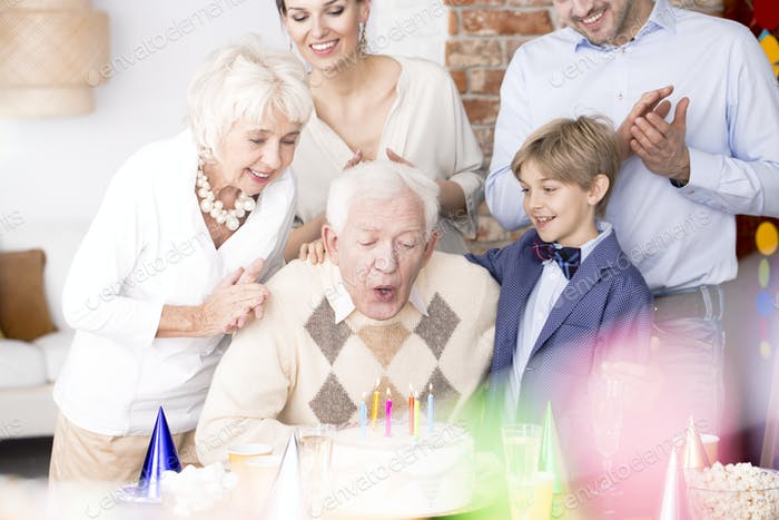 Grandpa blowing out candles on birthday cake