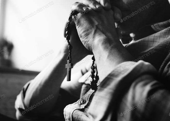 Cloesup of hands holding cross praying grayscale