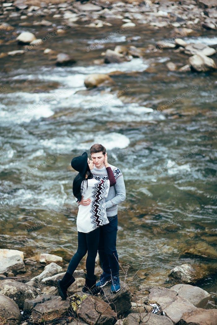 guy and girl along a mountain river