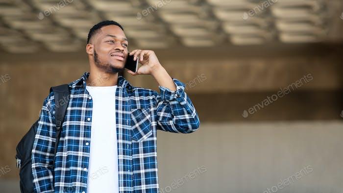 Черный человек, стоящий в городе, разговаривает по телефону