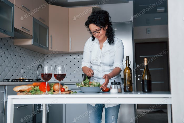 One person. Woman in white shirt preparing food on the kitchen using vegetables