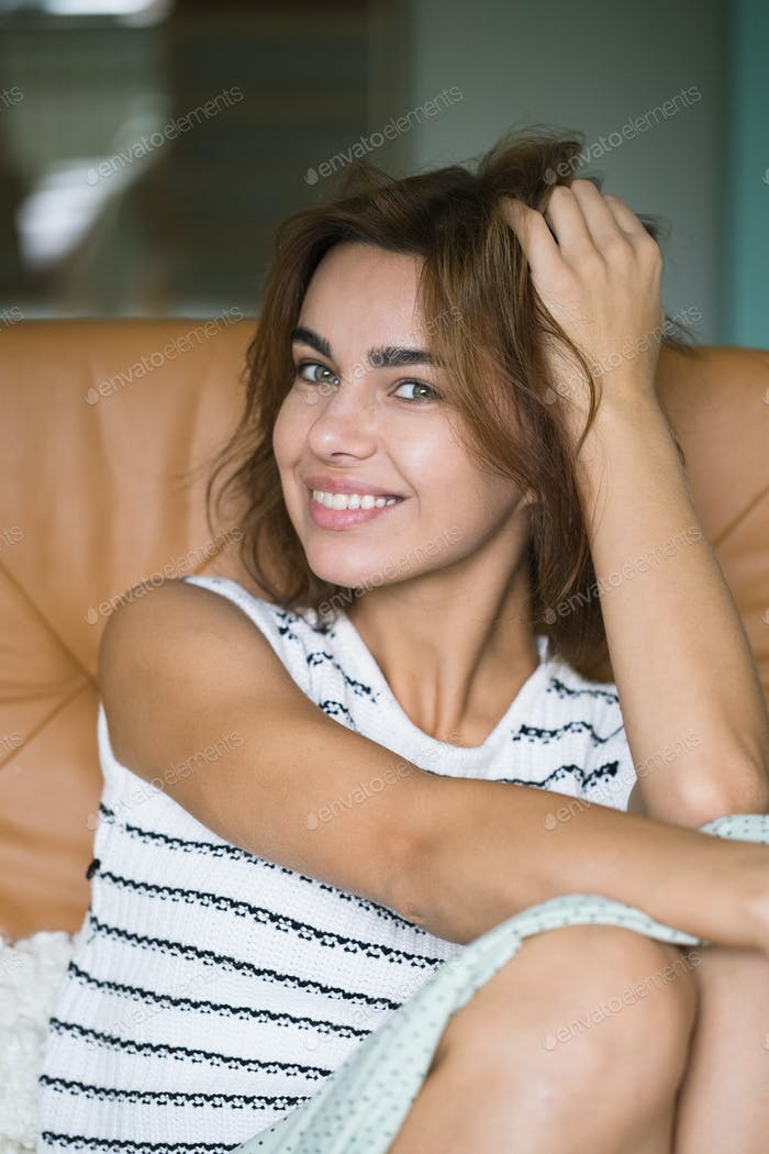Portrait of a young happy woman sitting on the sofa at home