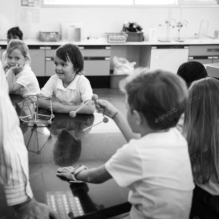 Diverse kindergarten students holding learning structures from t
