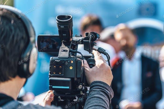 Kameramann bei einer Outdoor-Medienveranstaltung. Unscharfe Lautsprecher in der Rückseite
