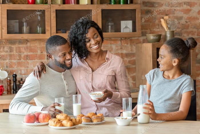 Adorable black family of three having breakfast at kitchen