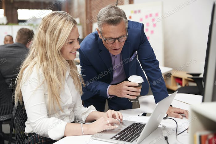Businessman And Businesswoman Working At Laptop On Desk In Open Plan Office