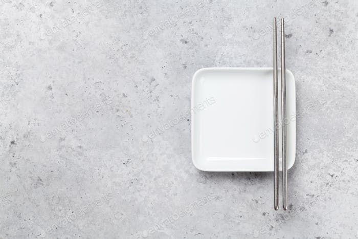 Empty plate and chopsticks over stone table