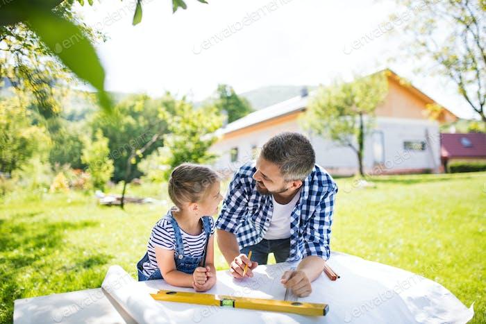Vater mit einer kleinen Tochter draußen, Planung hölzerner Vogelhaus.