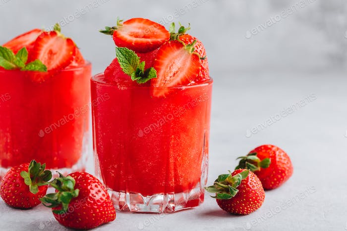 Fresh strawberry rhubarb and watermelon granita with mint on gray stone background