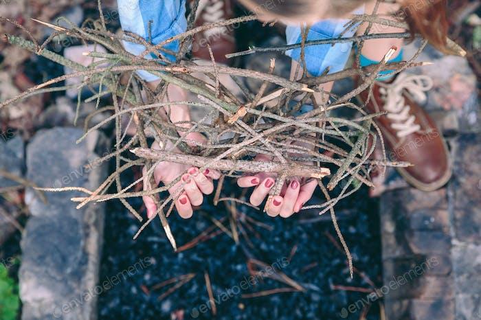 Weibliche Hände halten Brennholz für Lagerfeuer über Kohlen Hintergrund