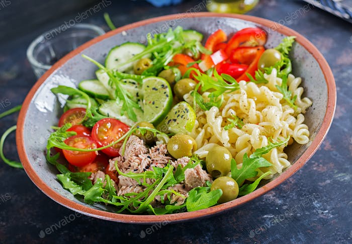 Pasta salad with tuna, tomatoes, olives, cucumber, sweet pepper and arugula