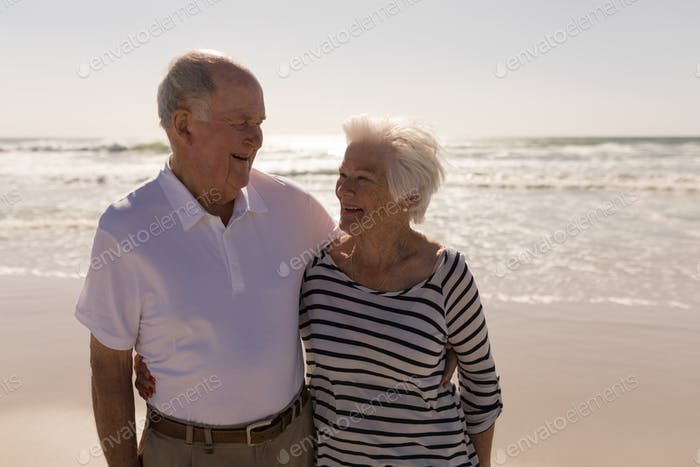 Front view of happy senior couple with arms around looking each other on beach in the sunshine
