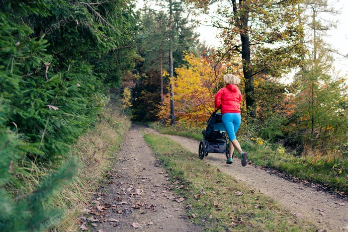 Running mother with stroller enjoying motherhood at autumn sunse