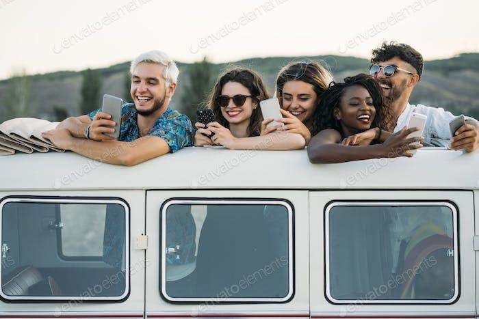 Friends using smartphones in van