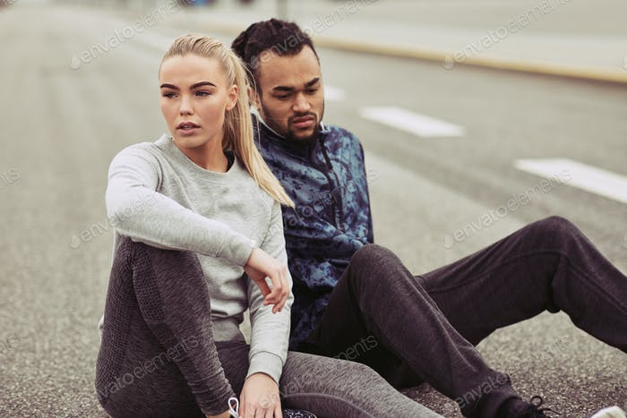 Exhausted young couple catching their breath during a run outdoors