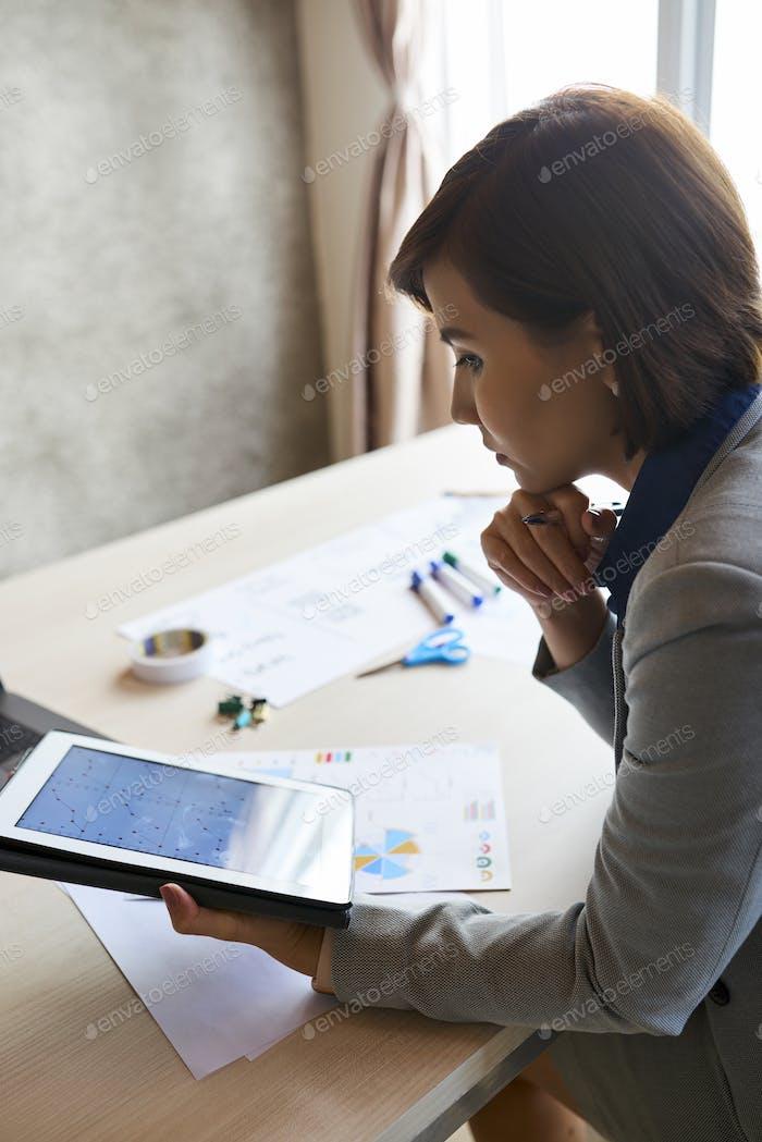 Pensive entrepreneur with tablet computer