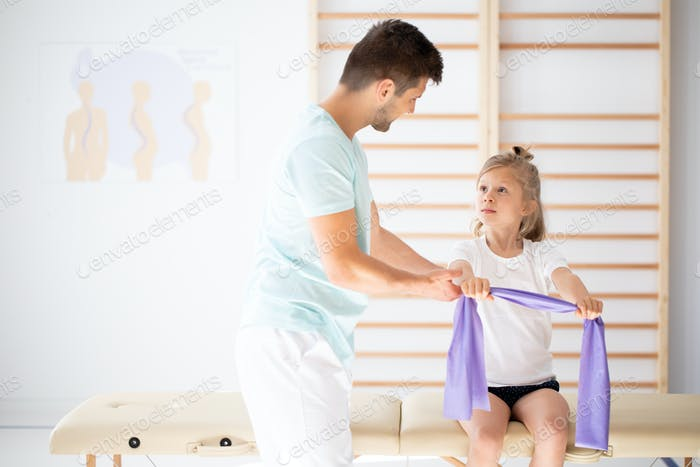 Professional physician explain to child how to perform an exercise