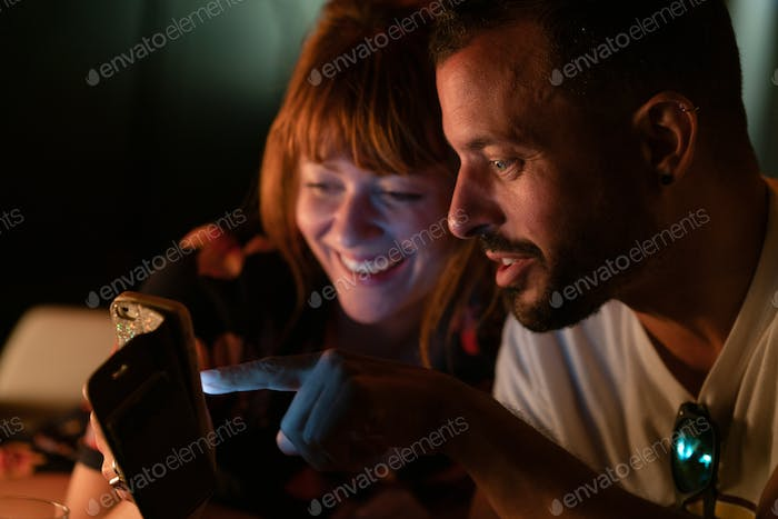 Ginger woman and man with beard looking at a phone and laughing