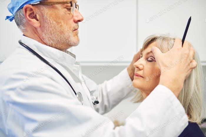 Plastischer Chirurg hält Kopf der erwachsenen Frau