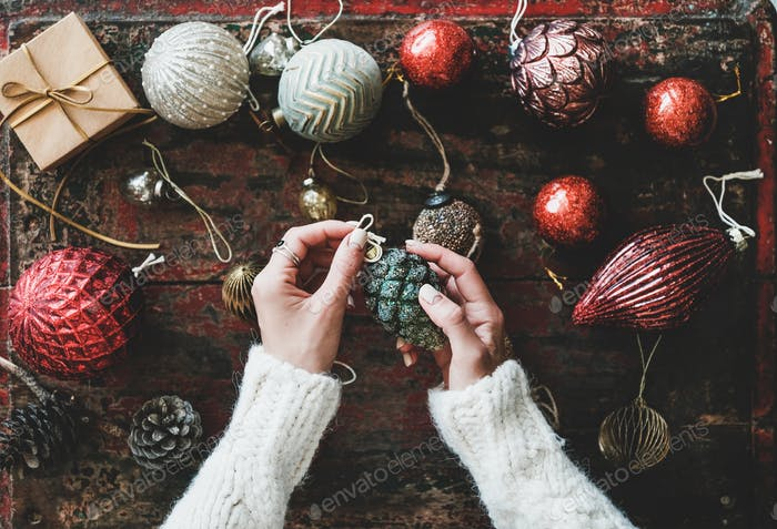 Christmas decoration toys and woman's hands over red wooden background