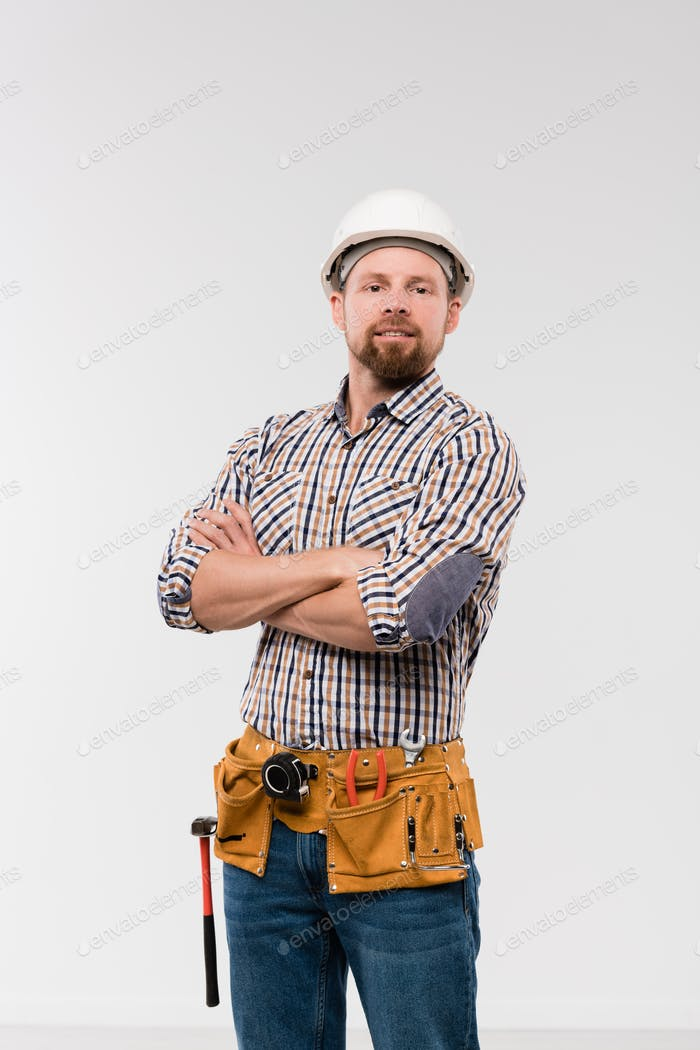 Young technician with toolbelt on his waist crossing arms by chest