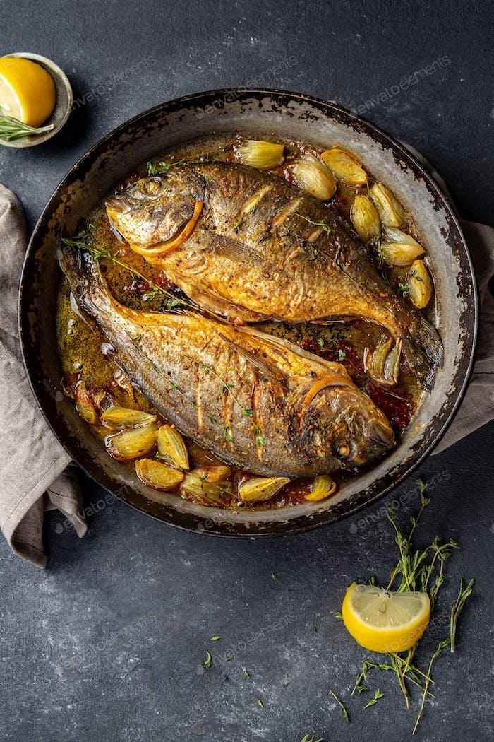 Besugo al horno o dorada con cebolla y hierbas en sartén sobre fondo oscuro.