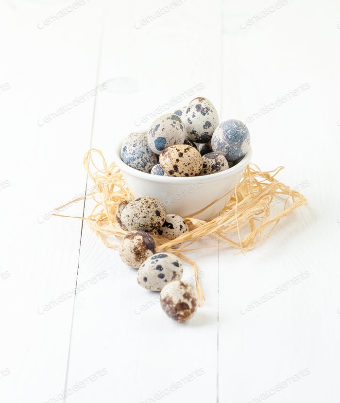 Fresh quail eggs in a white bowl on a wooden table.