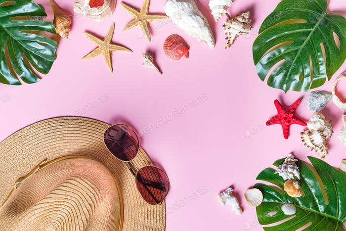Beach accessories: sea shell, starfish, tropical palm leaves, straw hat and sun glasses on pink