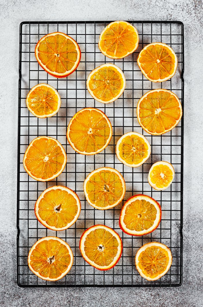 Dried thin translucent orange slices on pastry rack