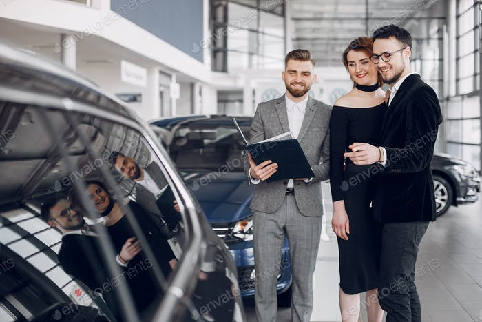 Stylish and elegant couple in a car salon