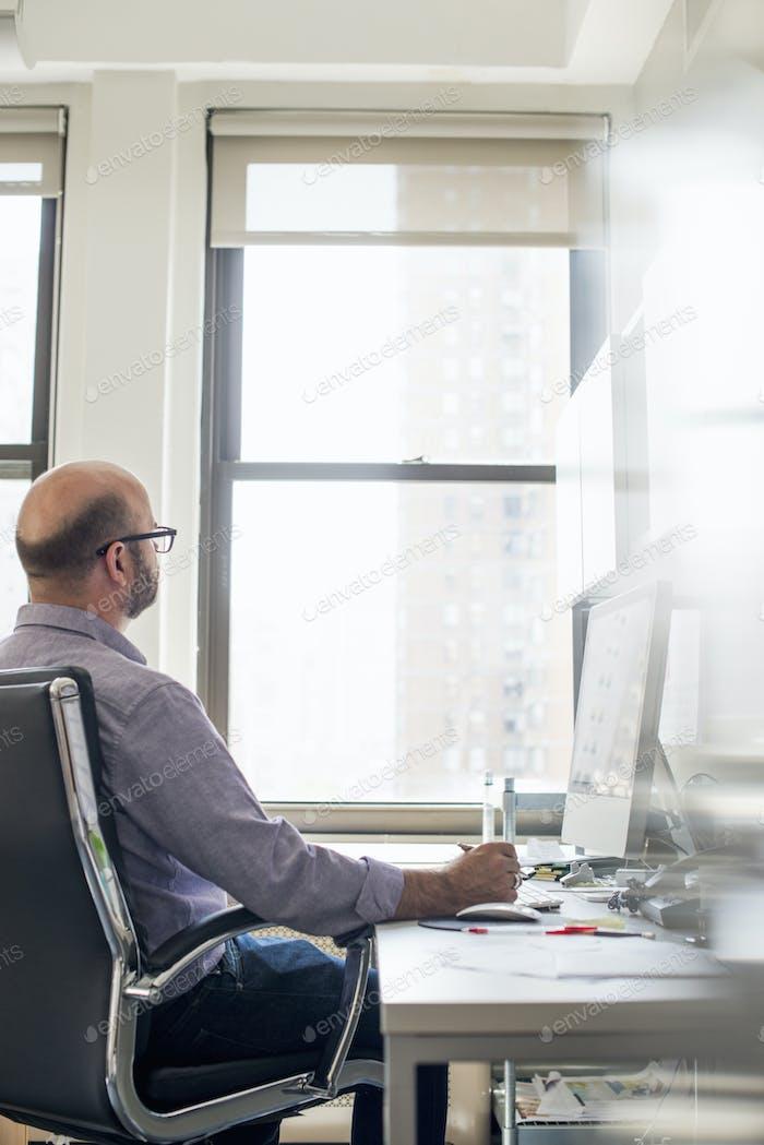 Büroleben. Ein Mann sitzt an einem Schreibtisch mit einem Computer und schaut aufmerksam auf den Bildschirm.