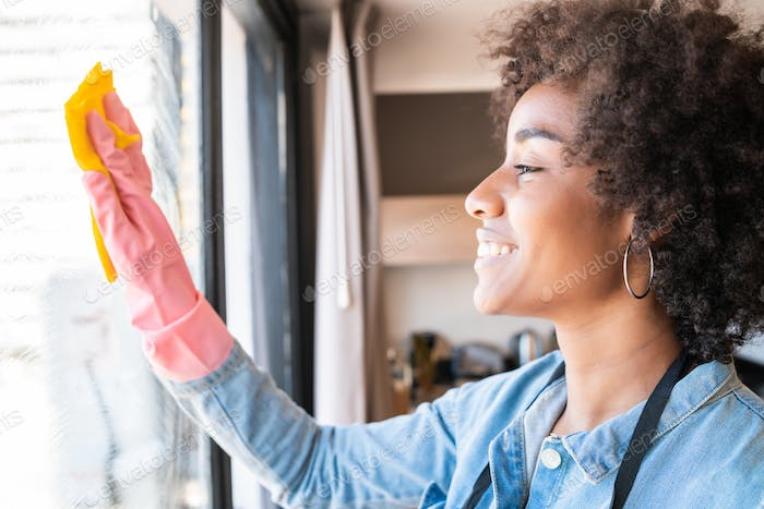 Afro woman cleaning window with rag at home.
