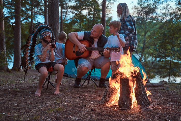 American family camping in woodland on weekend