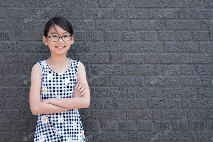 Portrait of young Asian girl against black brick wall