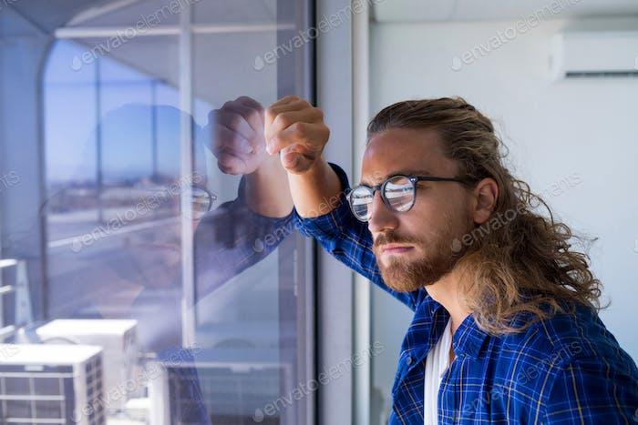Männliche Executive Blick durch Fenster im Büro