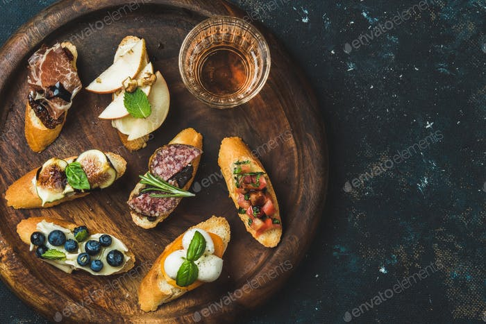 Italian crostini and glass of wine in wooden tray