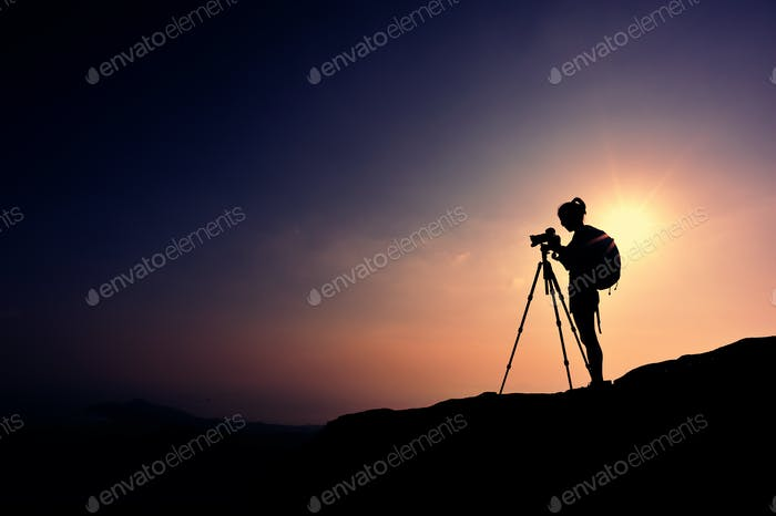 Female photographer on sunset mountain peak