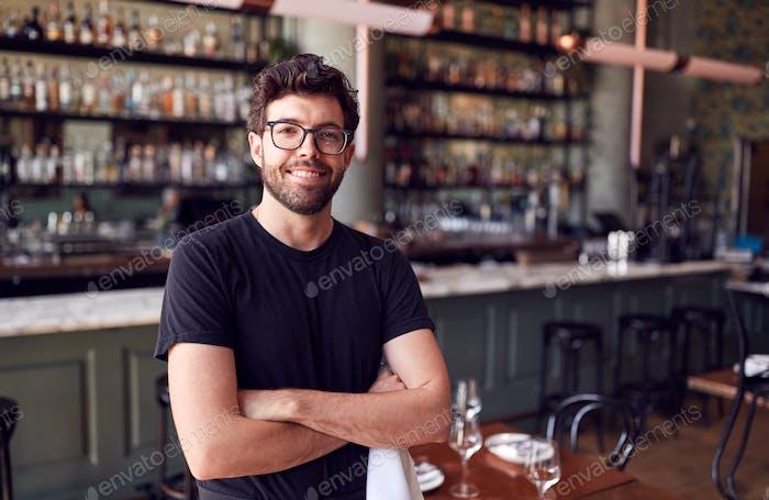 Portrait Of Male Waiter Standing In Bar Restaurant Before Service