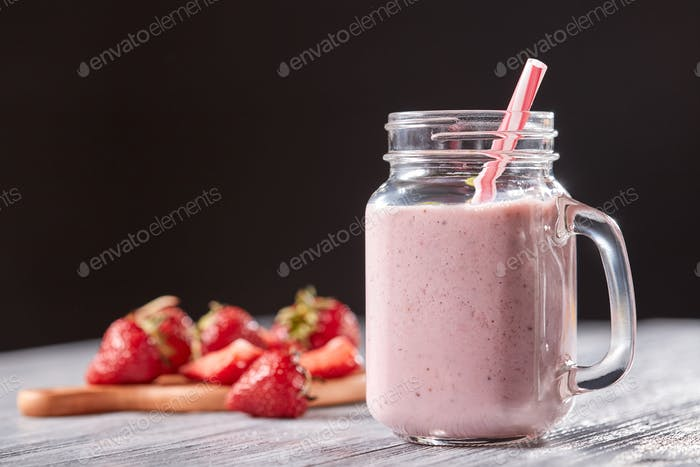 Homemade strawberry milk shake in a jar with a straw on a wooden table around a black background