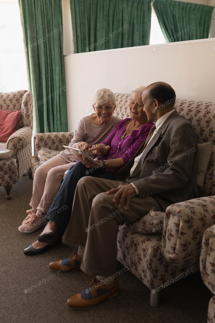 Front view of senior friends discussing over digital tablet while sitting on sofa at home